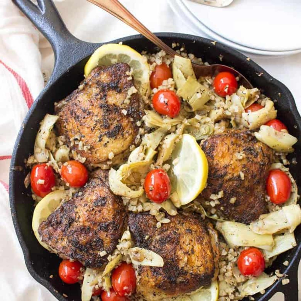 a skillet full of chicken thighs on a bed of vegetables, lemon slices and plum tomatoes