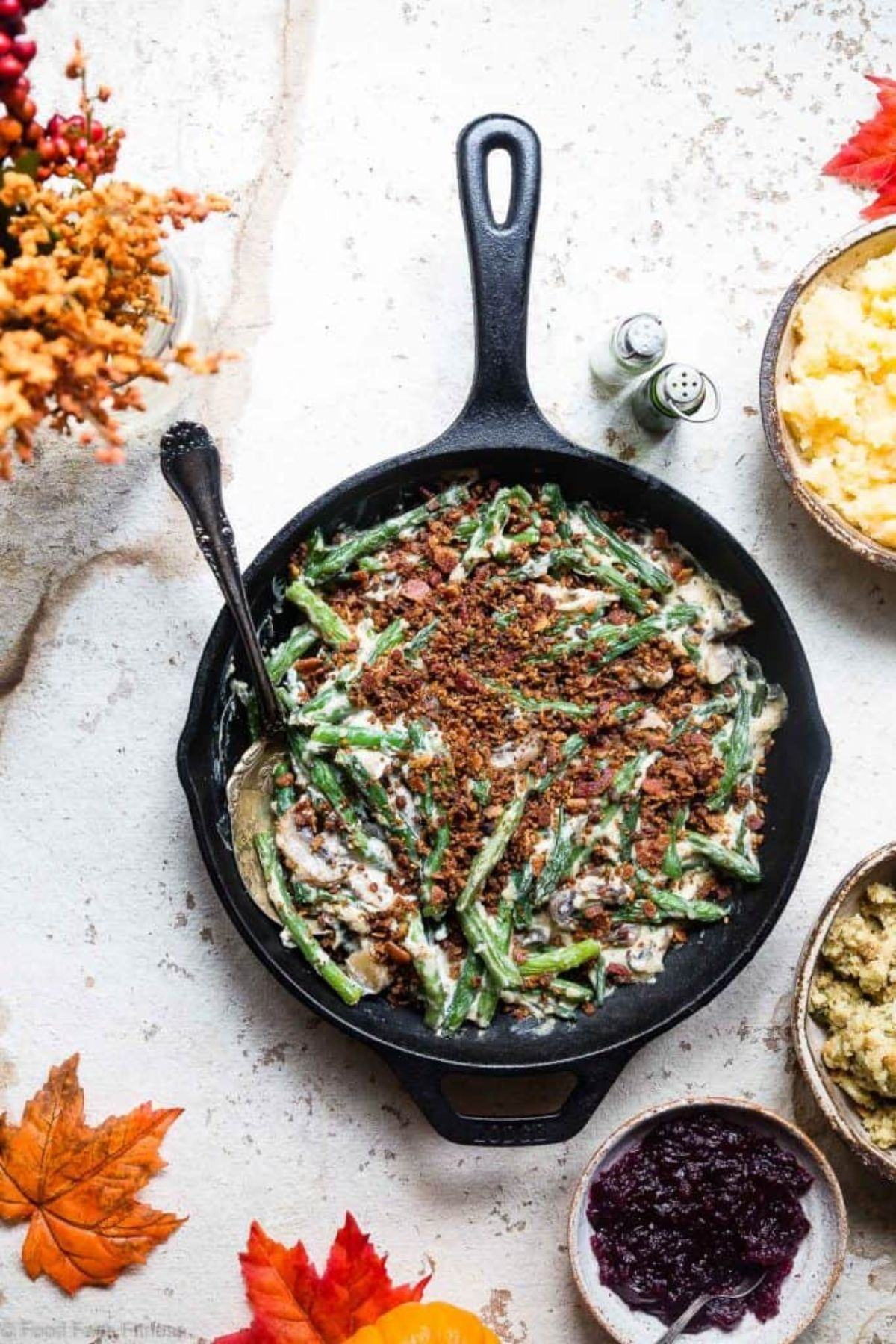 A cast iron skillet filled with green bean casserole, sprinkles with bacon crumble.