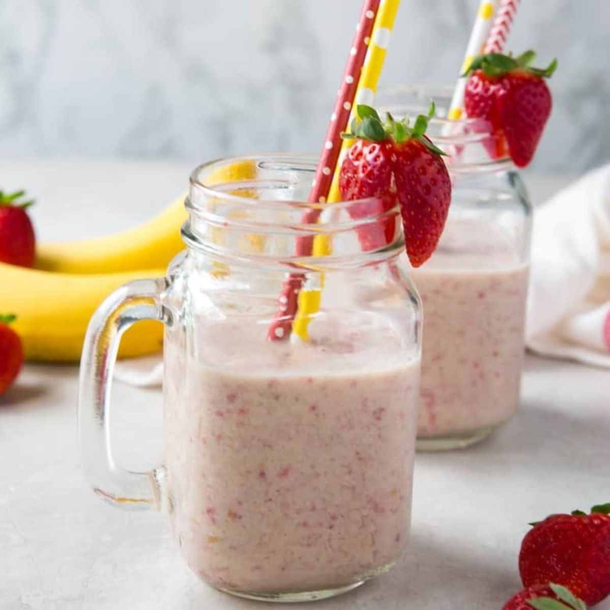 2 squared mason jars with strawberry banana smoothie in them, garnished with whole strawberries and each with a red and yellow straw in them