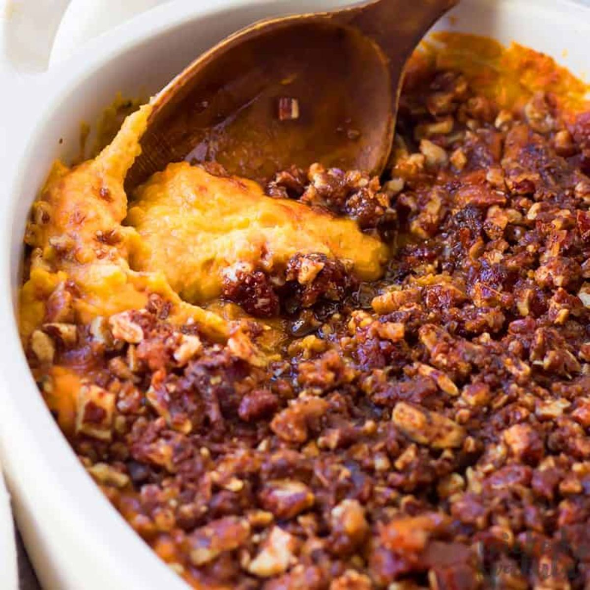 a partial shot of a casserole dish filled with sweet potato casserole, a wooden spoon is sticking out of it