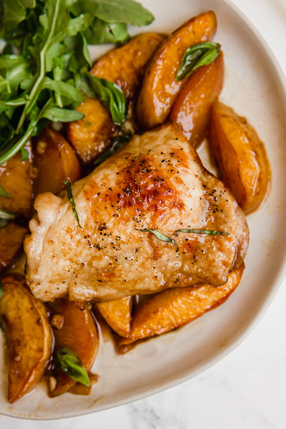 a partial shot of a plate of chicken thighs, sliced peaches and arugula