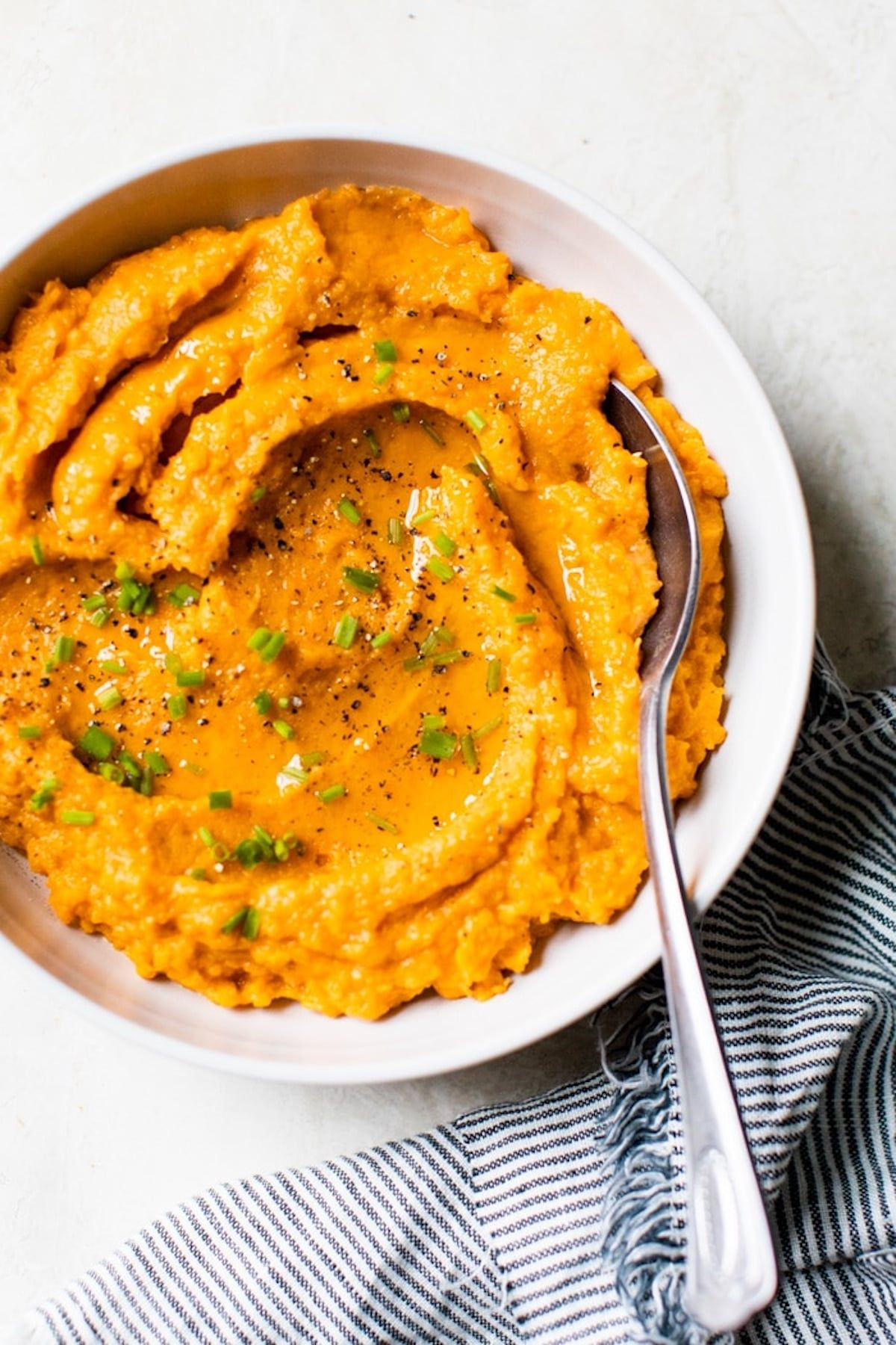 a white bowl of sweet mashed potatoes, with a spoon stuck in it