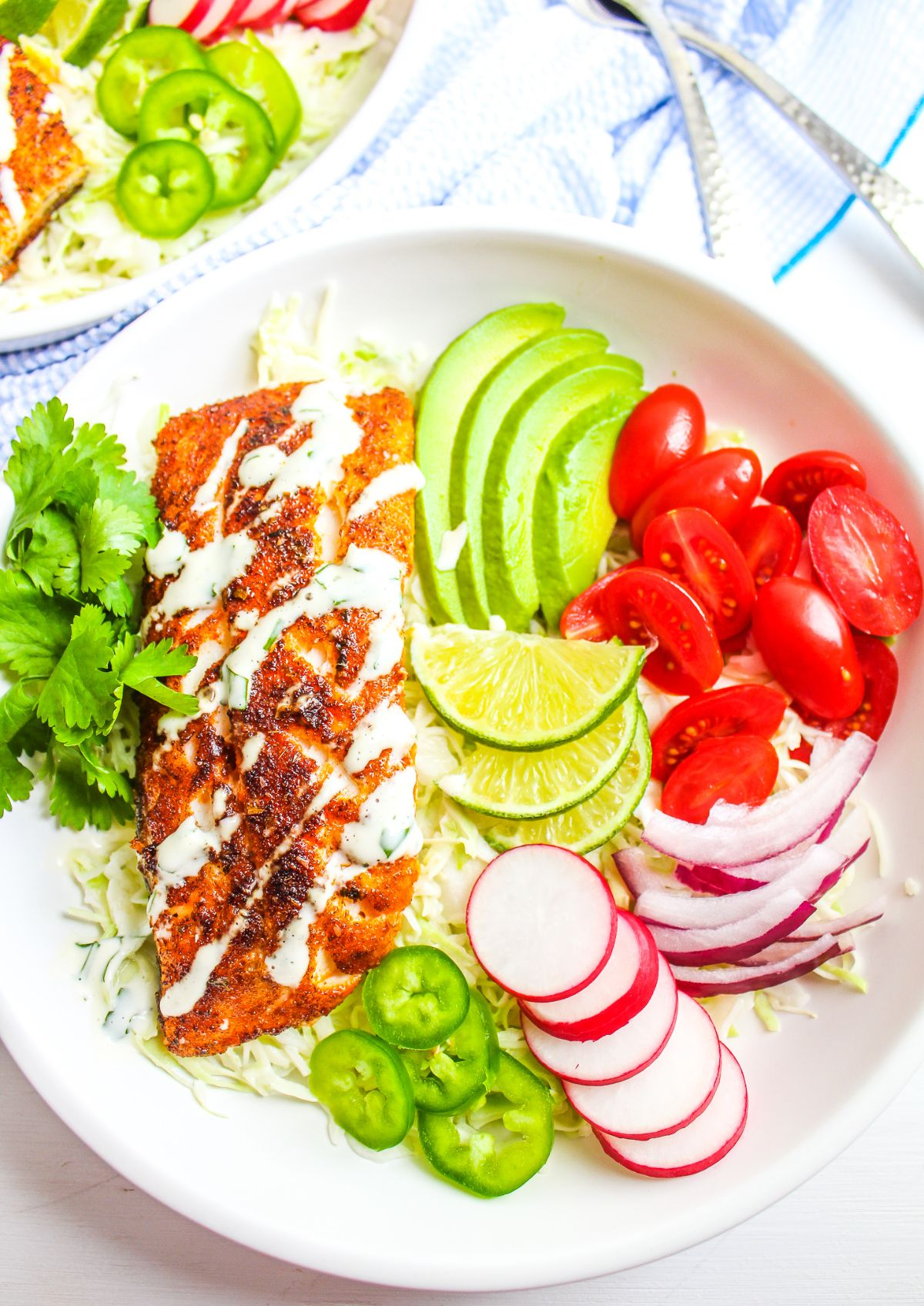 a plate of fish fillet, sliced pear, tomoateos, sliced jalapenos, sliced radish and lime
