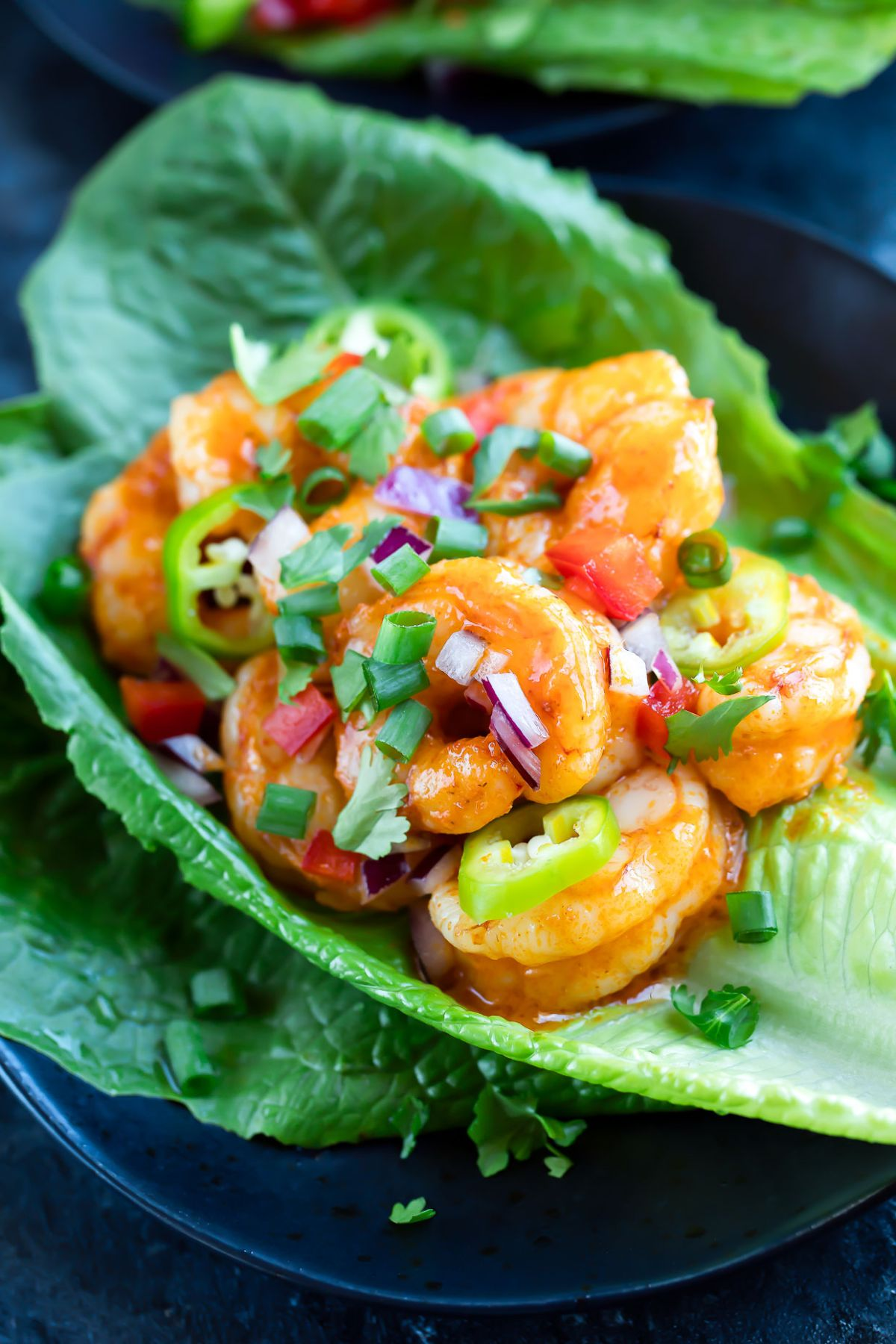 A close up of a lettuce cup filled with shrimp and sliced jalapenos sprinkled with chopped red onion and scallions