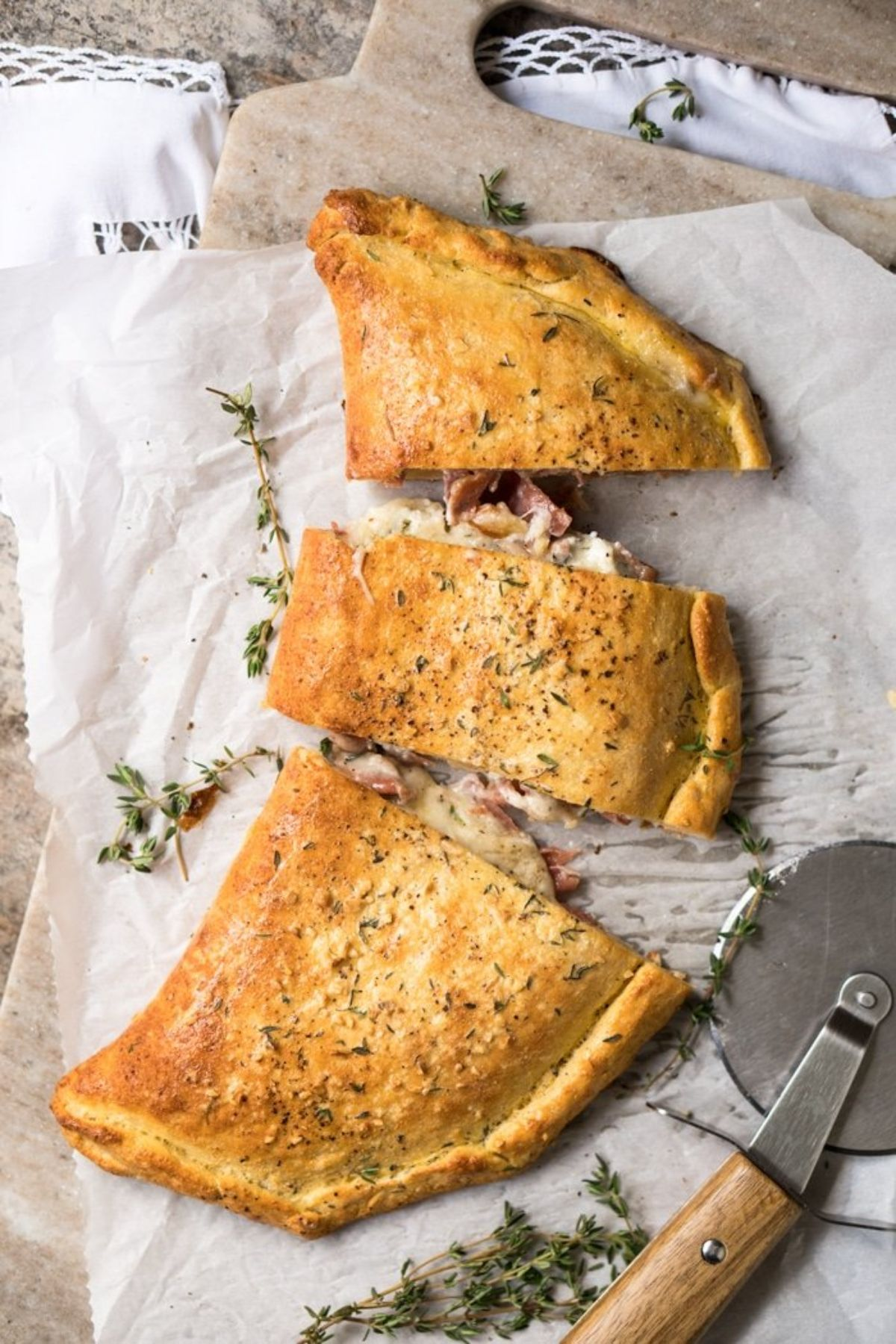 a calzone sliced into 3 pices with a pizza wheel on a baking parchmetn and board