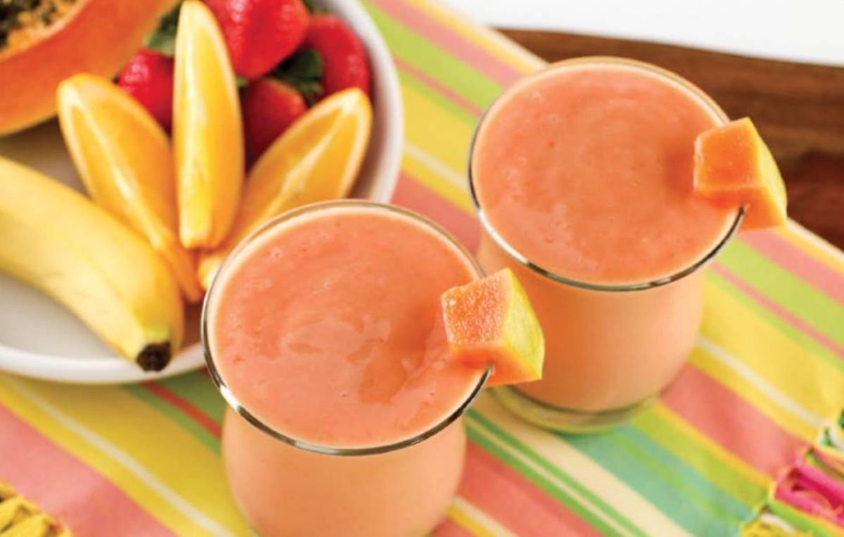 2 glasses of carribean sunset smoothie garnsihed with papaya chunks and next to a bowl of fresh fruit