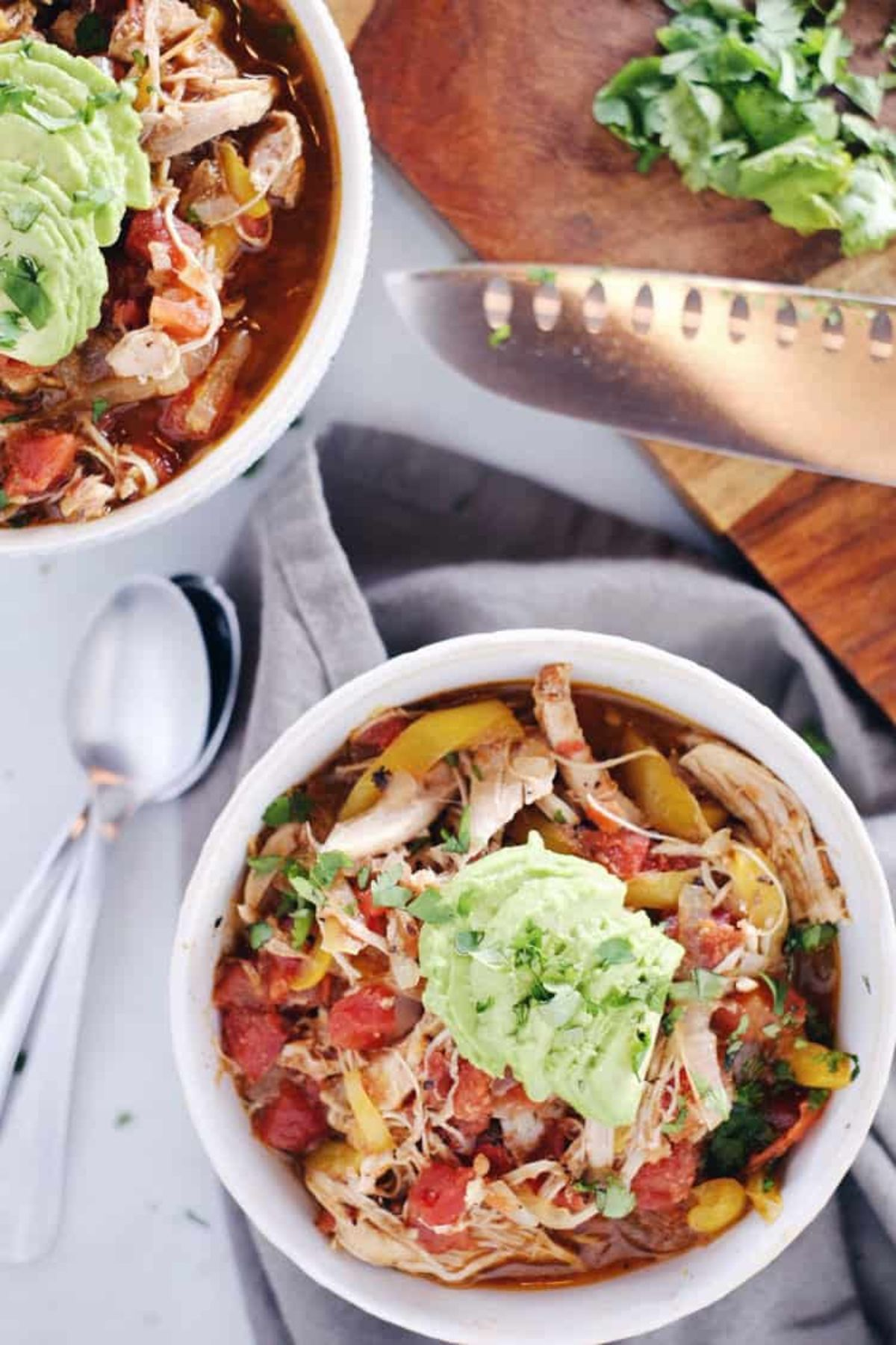 2 bowls of chicken soup with vegetables, topped with avocado and chopped herbs. silver spoons and a chopping knife sit on either side