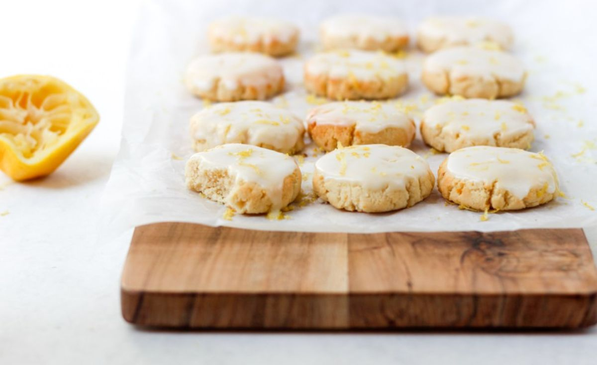 a wooden board with 12 iced lemon cookies on it, with a squeezed lemon half to one side