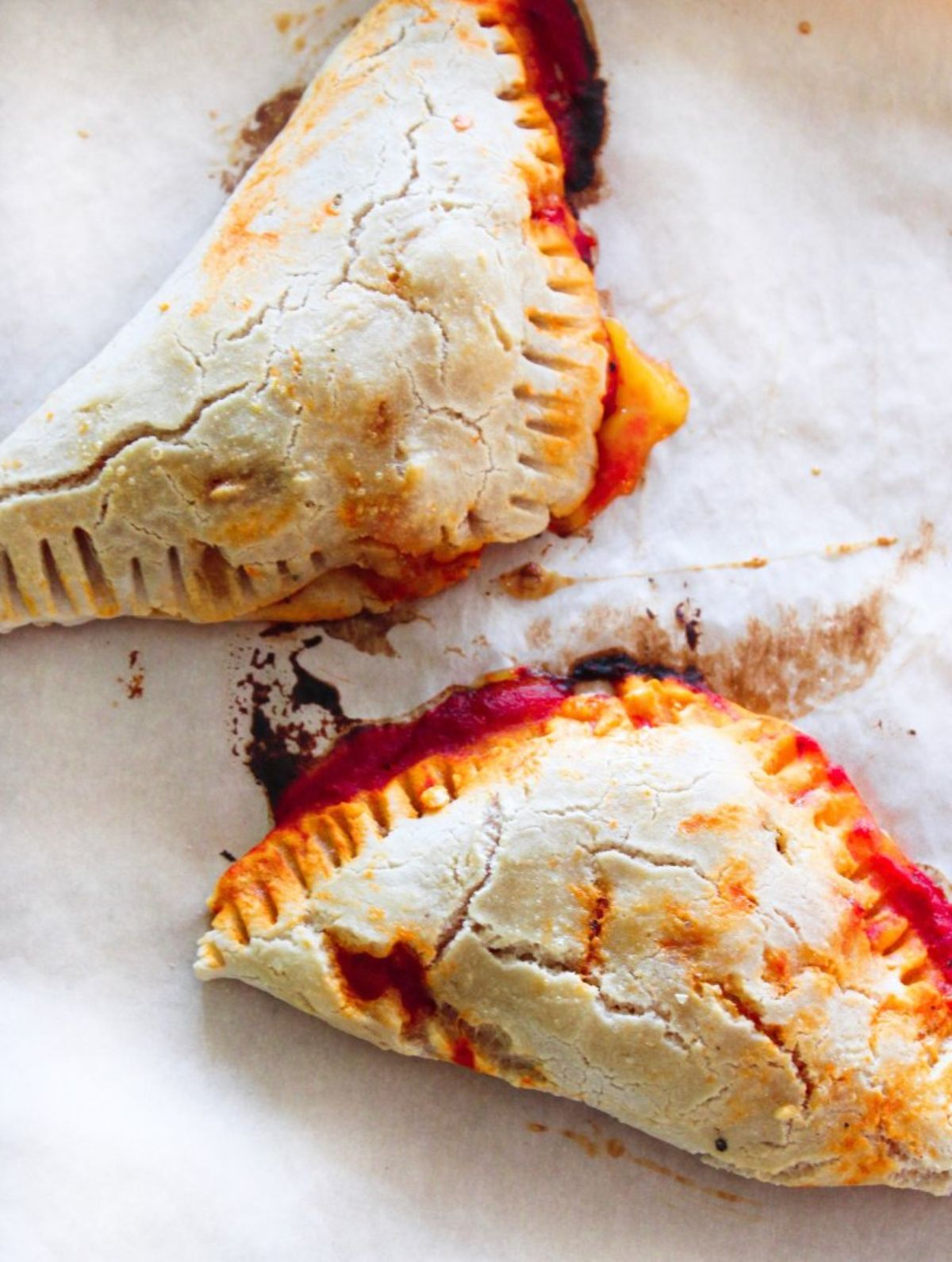 2 pizza pockets with red sauce oozing out of the sides