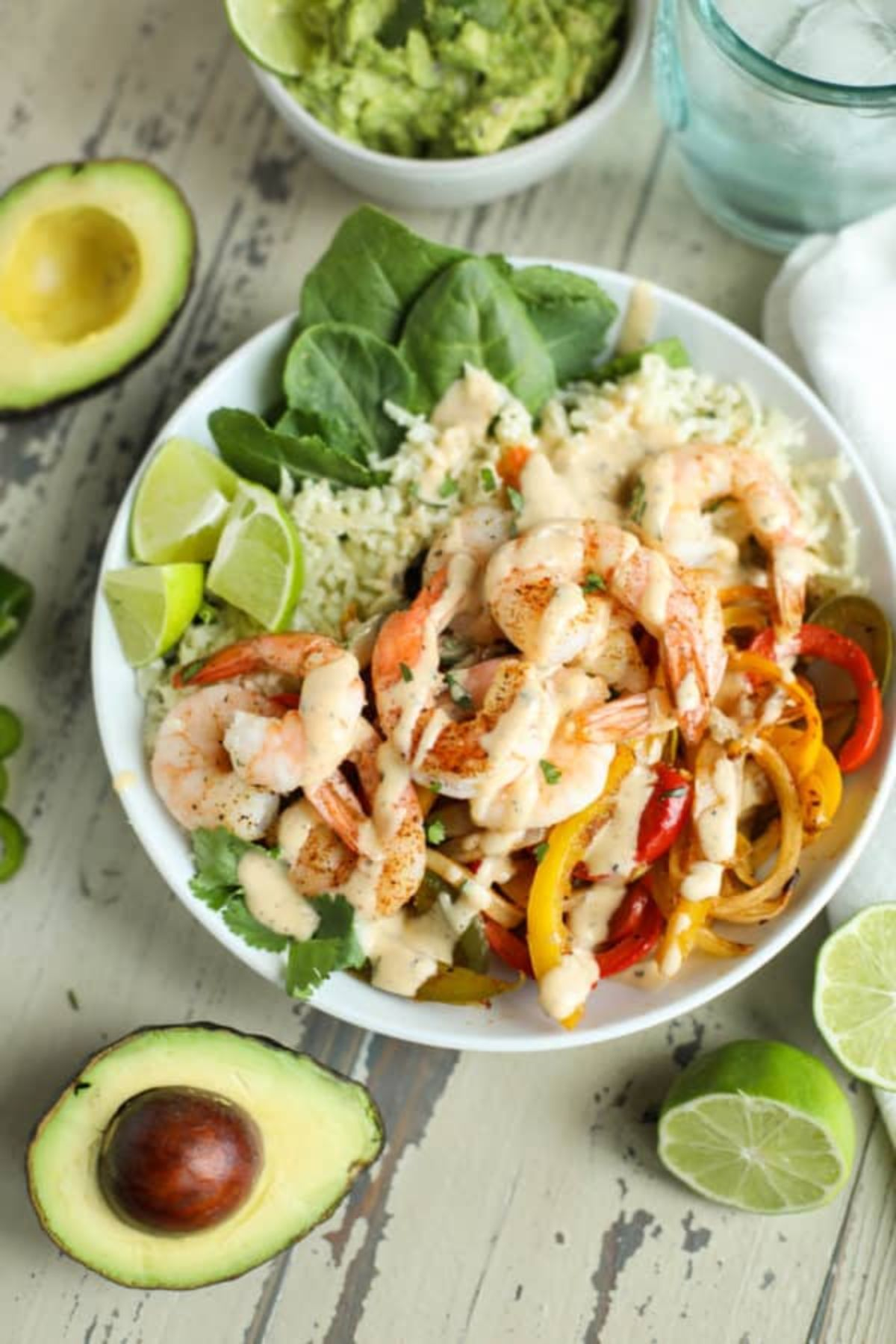 a bowl of rie with shrimp and sliced peppers on top, drizzled with reamy sauce and garnished with lime wedges. Halved avocados, lime wedges and a bowl of guacamole on the side