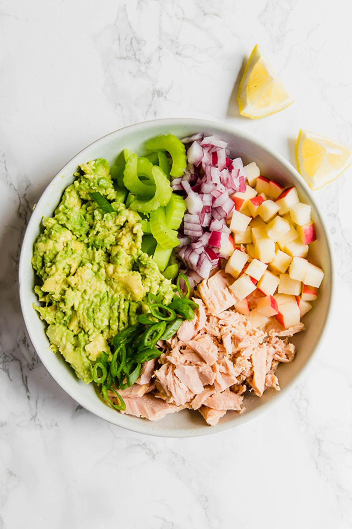 a bowl of avocado tuna salad with lemon wedges on the side