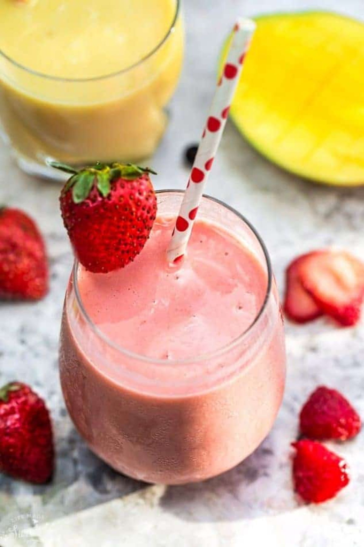 A glass of strawberry smoothie garnished with a strawberry and with a paper white and red straw in it. fresh strawberries are scattered around