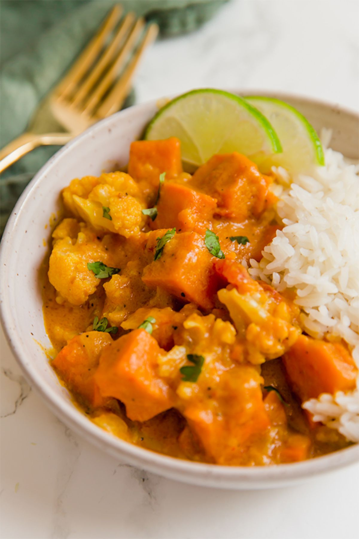 A white bowl of sweet potato cauliflower curry with lime slices and rice.