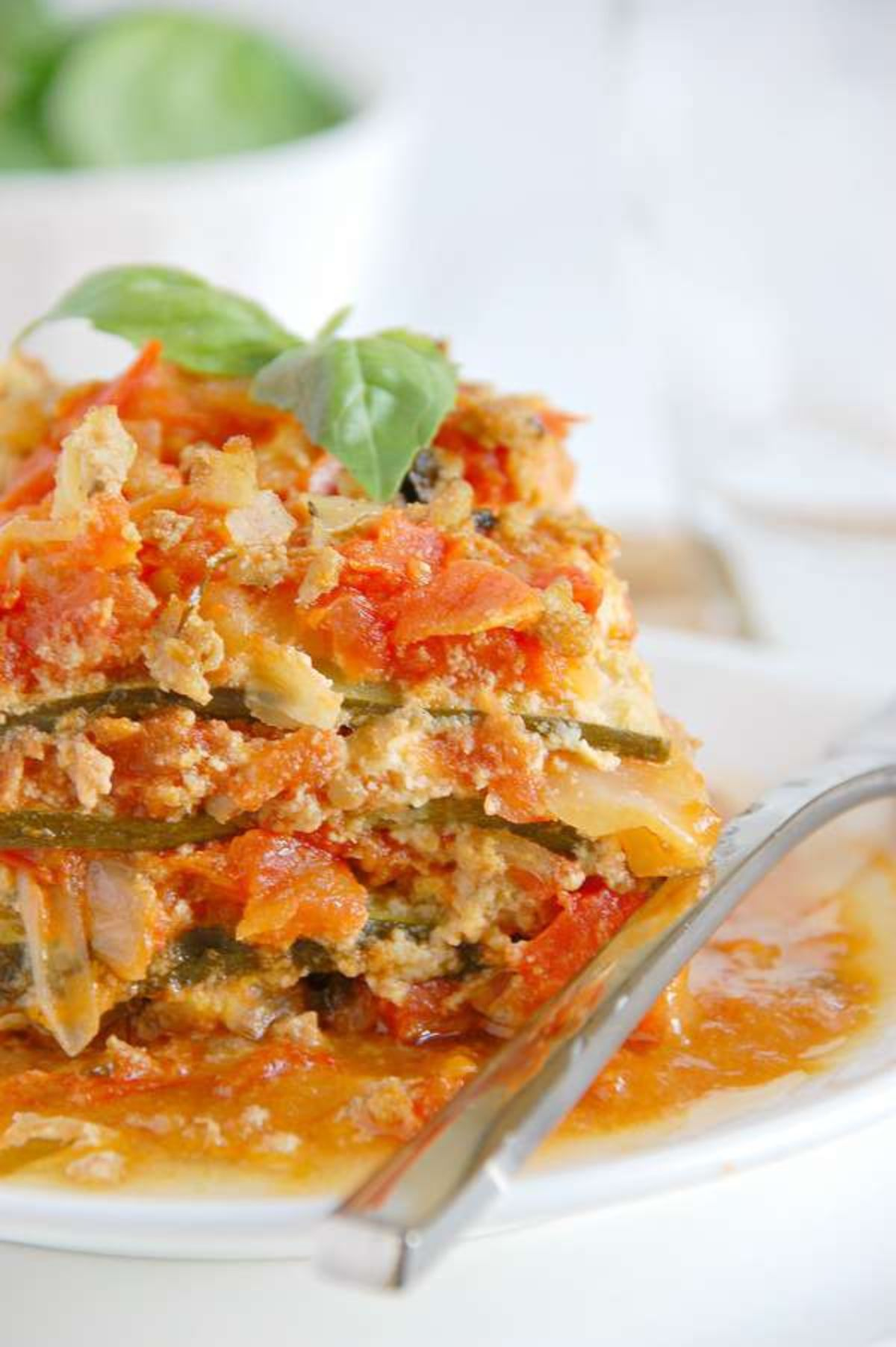A partial shot of a plate with a portion of zucchini lasagne and a kinfe