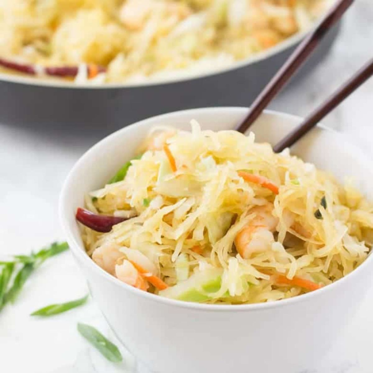 White bowl filled with noodles, shrimp and vegetables. Chopsticks are stickign out of the bowl