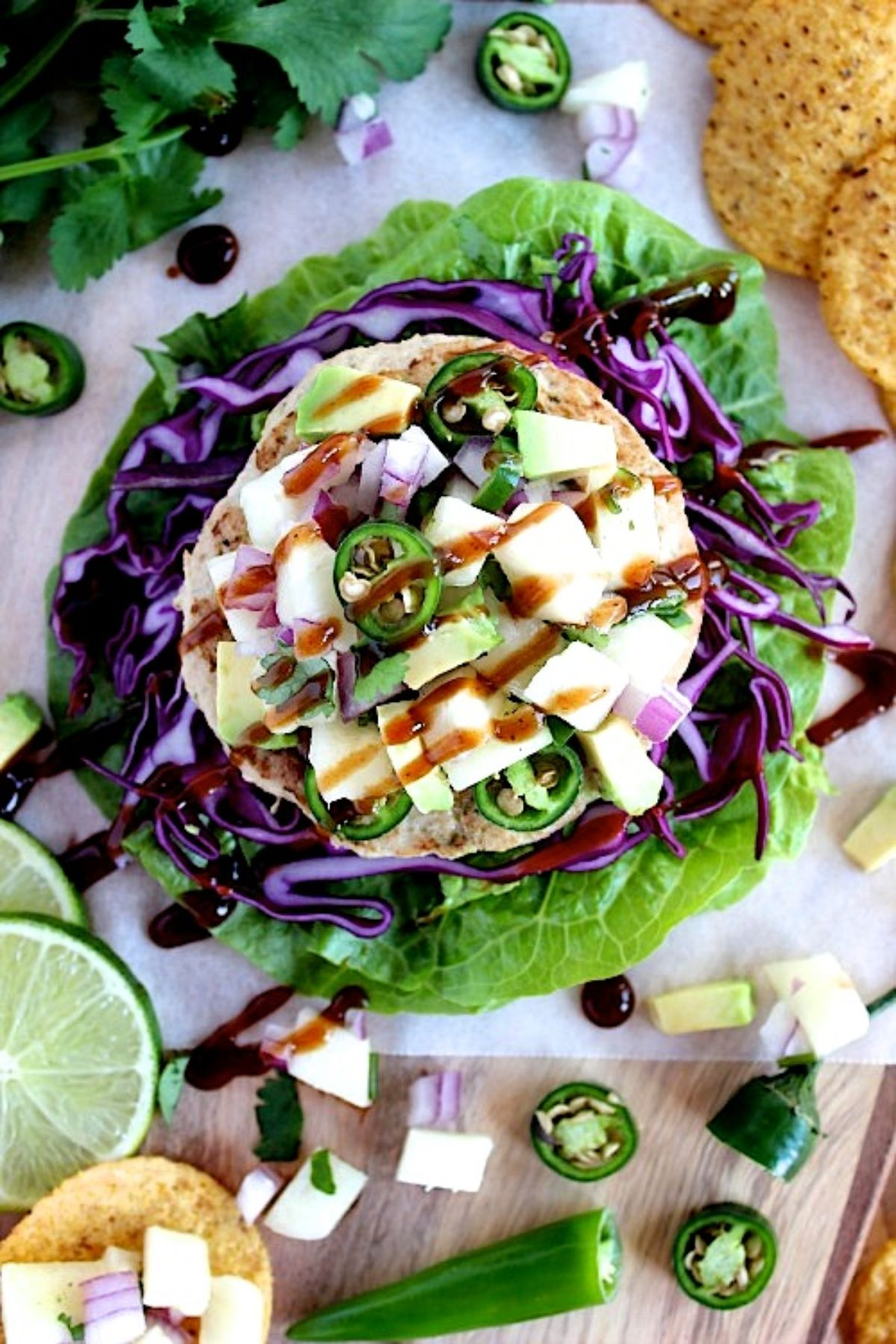 A lettuce leaf acts as a platter for a turkey burger topped with cheese, jalapeno slices and a brown sauce. Ingredients are scattered around it