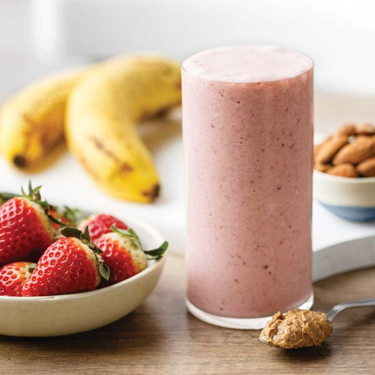 a glass of almond butter smoothie, next to a bowl of strawberries, 2 bananas and a bowl of almonds
