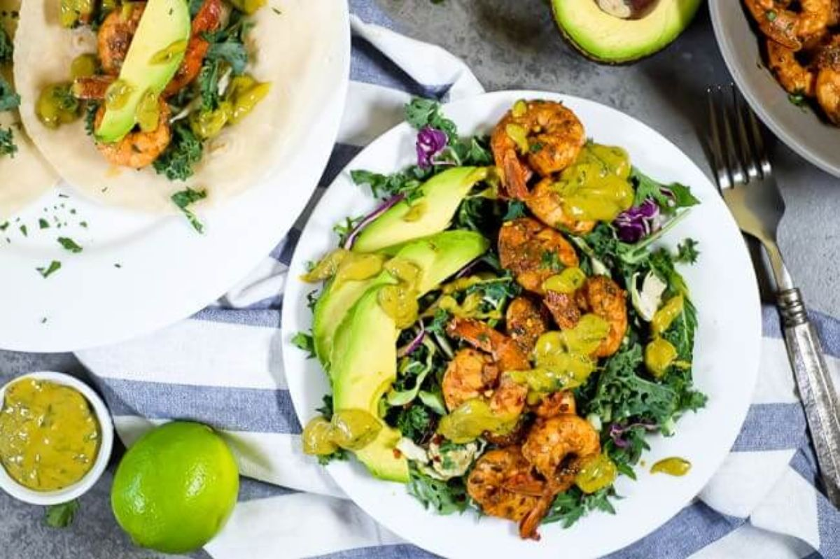 A white plate with kale, shrimp, avocado and lime sauce srizzled over it. THe plate is on a blue and white striped cloth