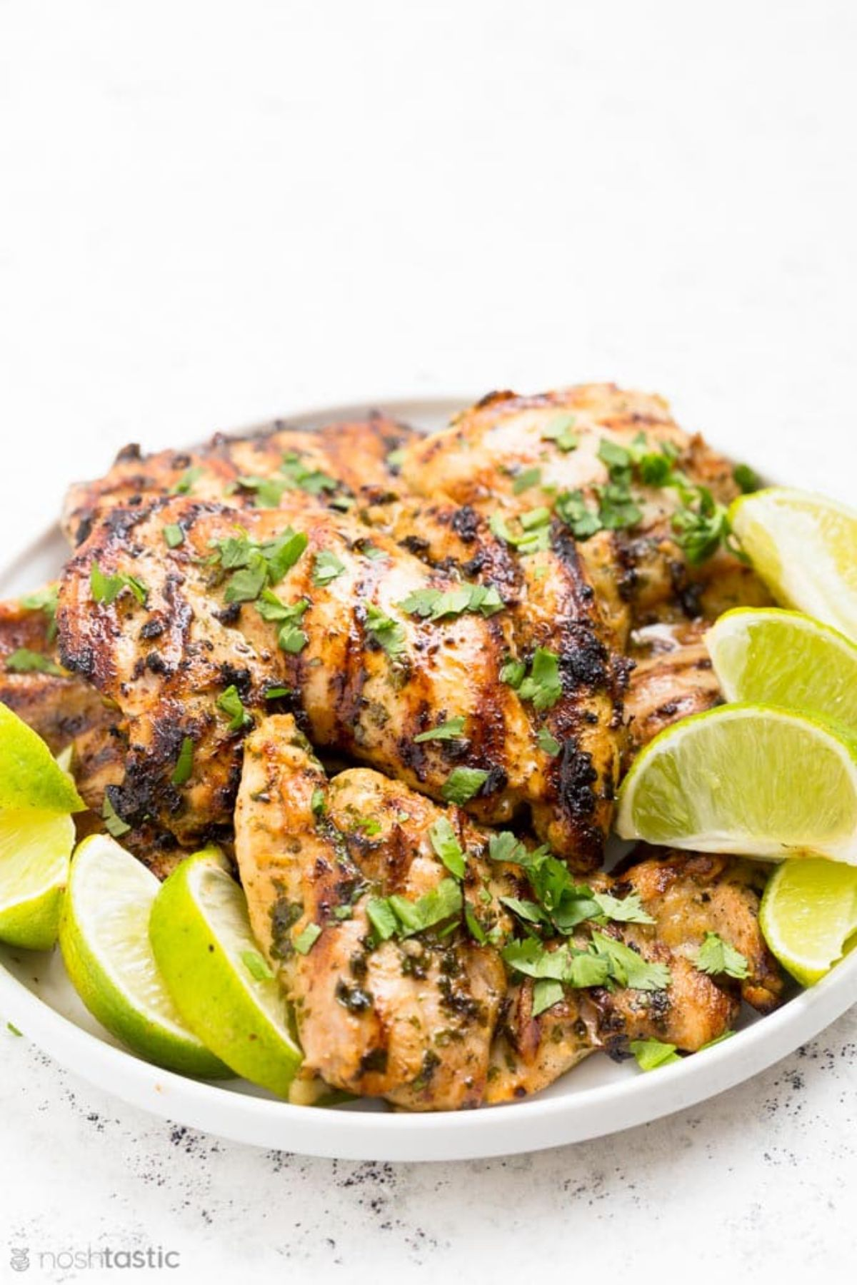 A plate of roasted chicken thighs garnished with chopped herbs and lime wedges