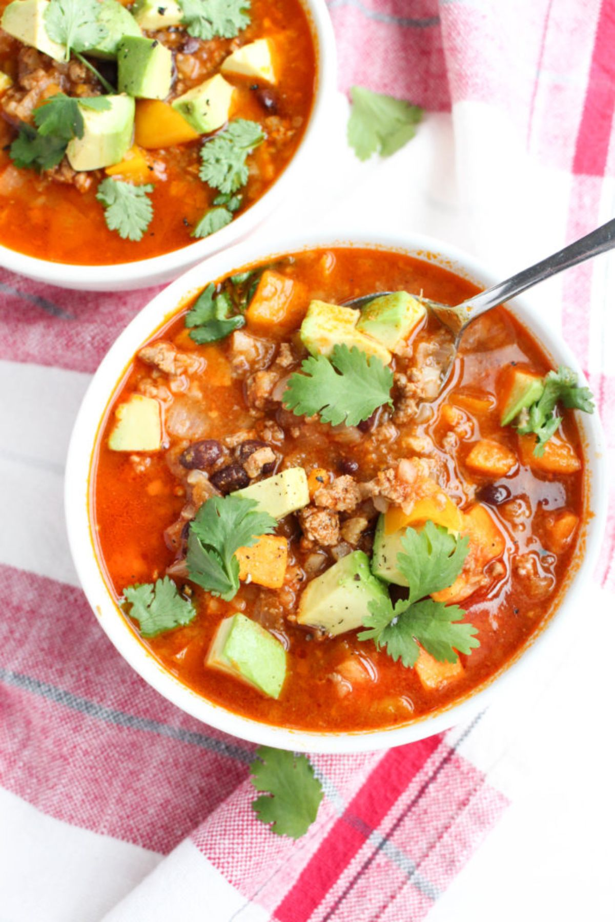 2 white bowls of taco soup toppped with avocado and herbs, a silver spoon resting in one bowl