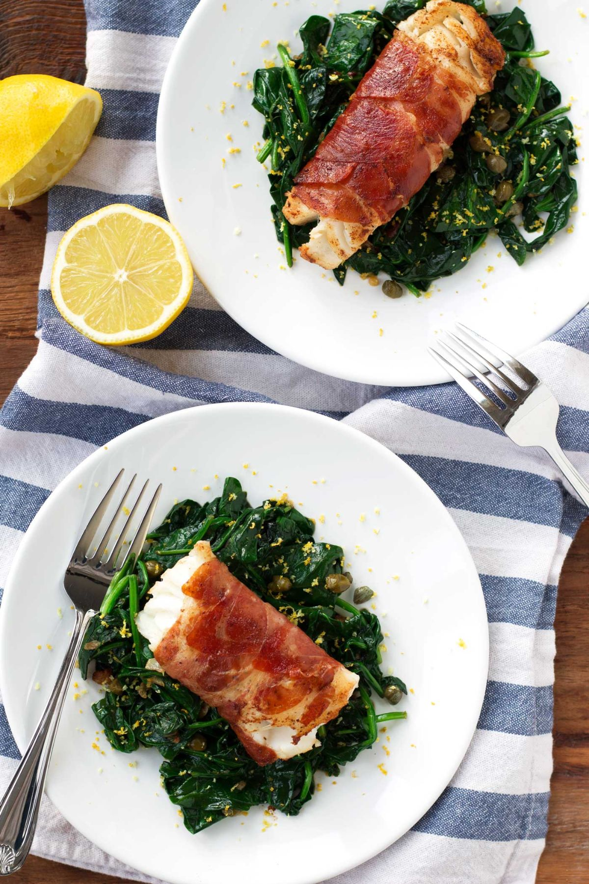 2 plates of proscuitto-wrapped cod on a bed of spinach