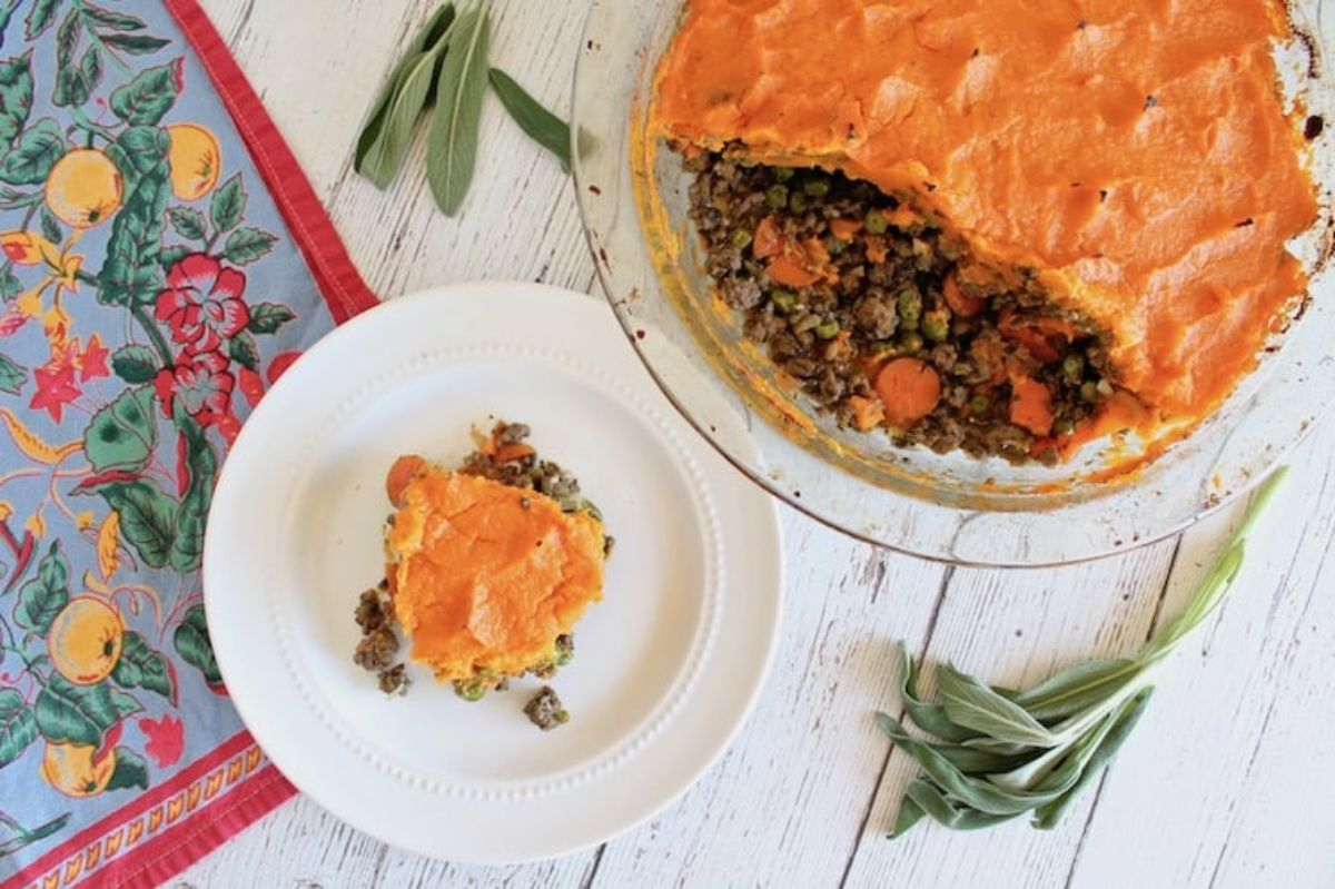a glass casserole dish with sweet potato shepherd's pie. next to it is a small plate with a portion of the pie on it