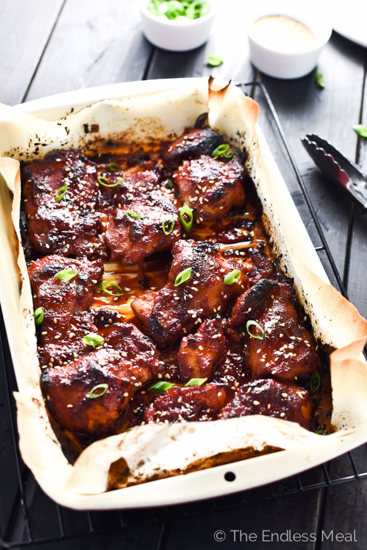 A paper-lined baking tray filled with korean chicken thighs and topped with sliced scallions and sesame seeds
