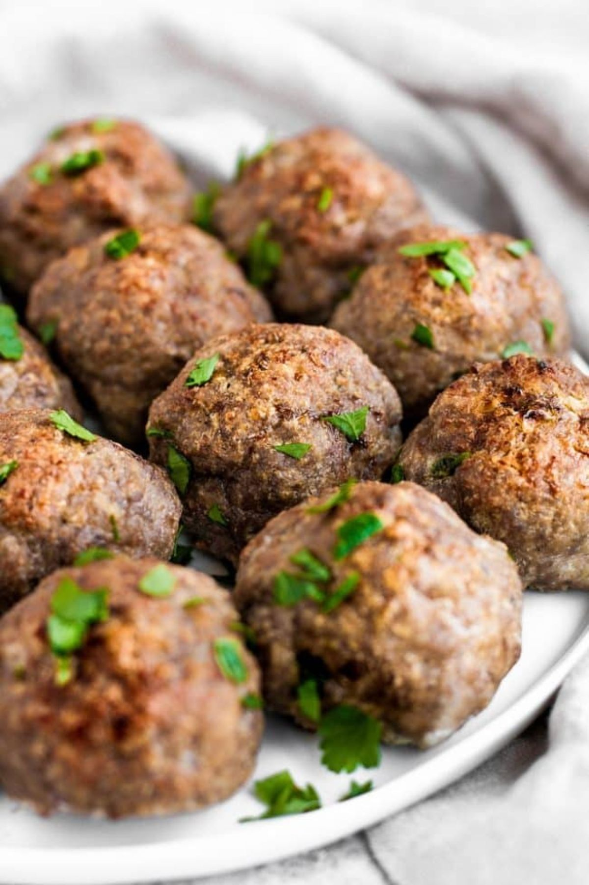 Meatballs on a white plate sprinkled with chopped herbs