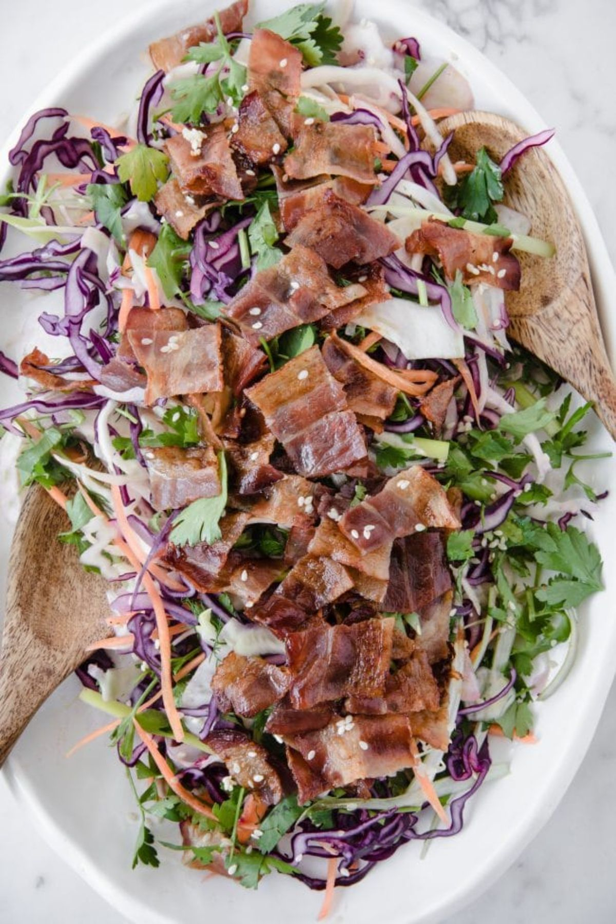 An oval white dish with bacon and salad. A wooden spoon is resting on both sides