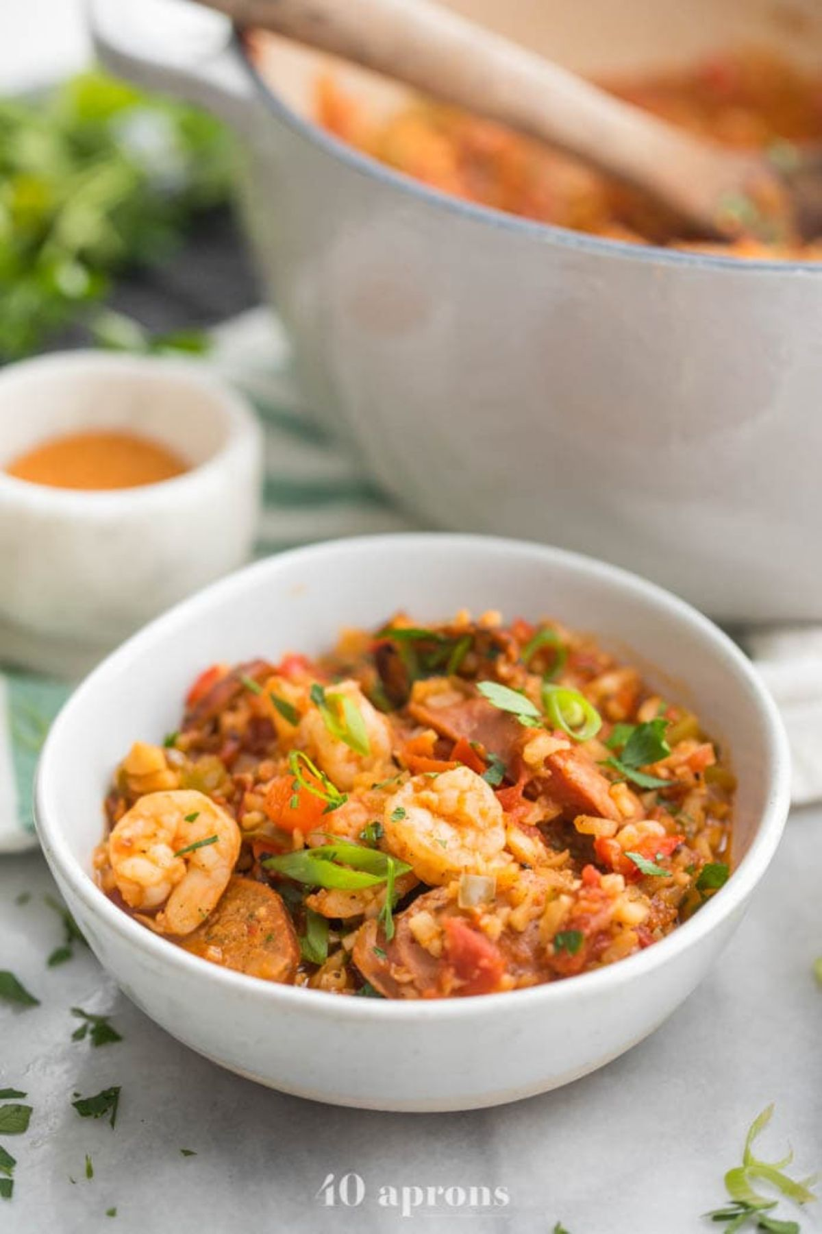 a white bowl of jambalaya, with a large pot of the same dish behind it