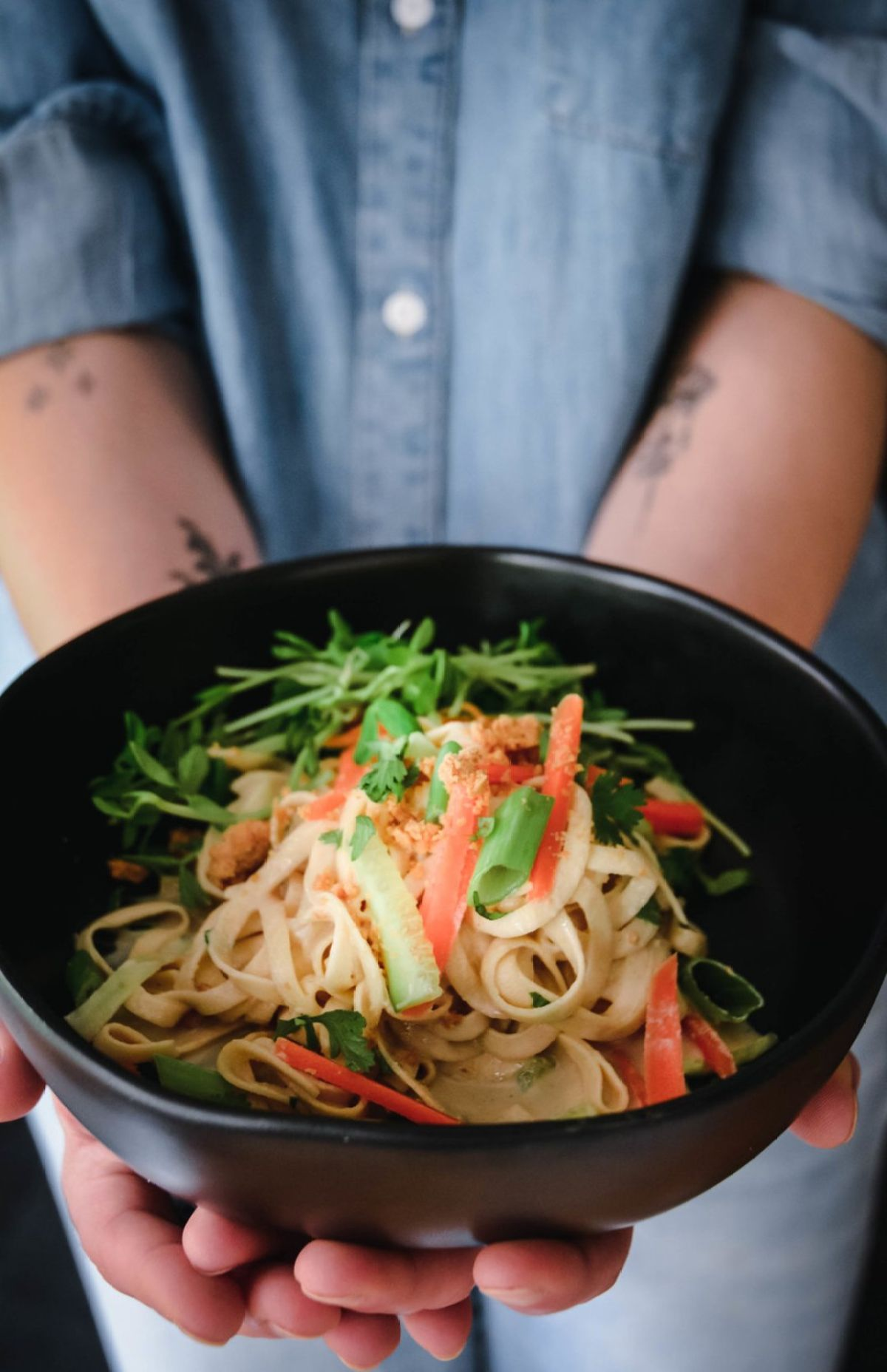 Two hands hold a black bowl containing rutabag oodles, and spiralized vegetables