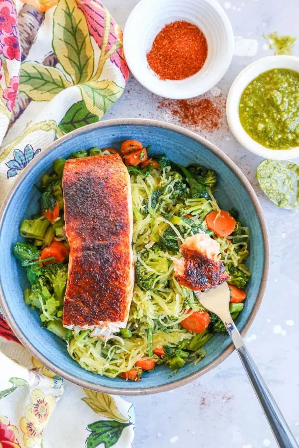 a blue bowl od spaghett squash noodles, with chopped vegetables and a fillet of salmon on top. 2 white bowls of spices and sauces are to the side