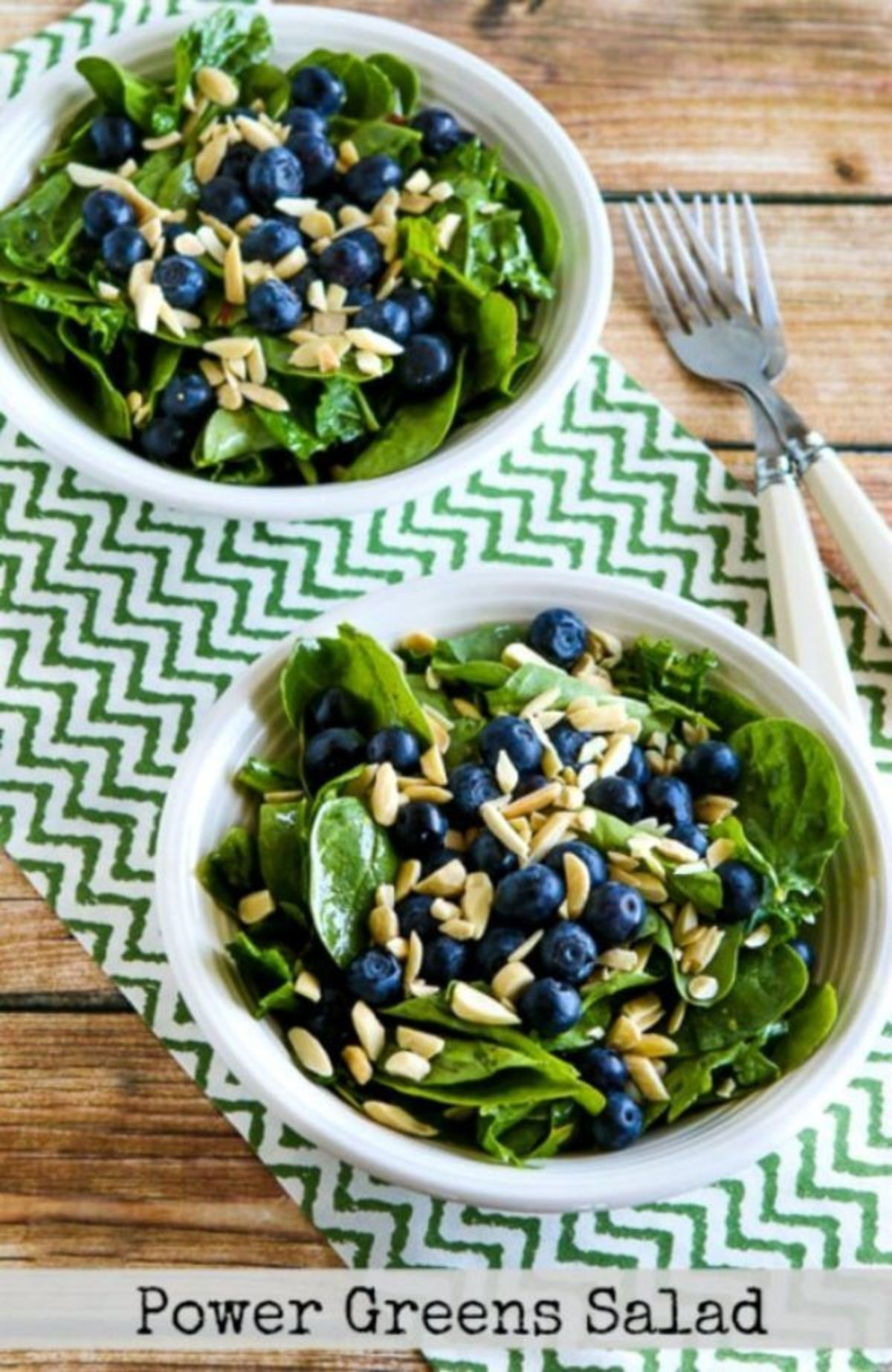 2 white bowls of green leaves, blueberries and chopped nuts, 2 forks by the side