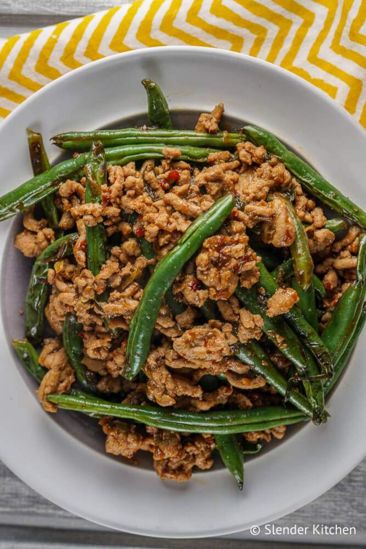 A white plate of ground turkey and green beans
