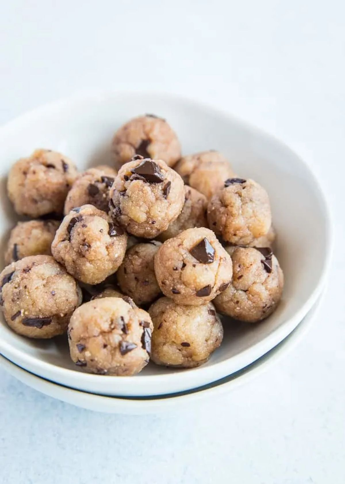 A white bowl with cookie dough balls in it