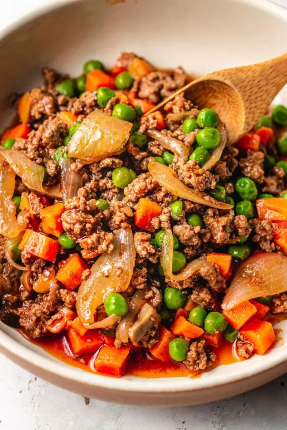 A bowl of ground beef and vegetables in sauce with a wooden spoon sticking into it