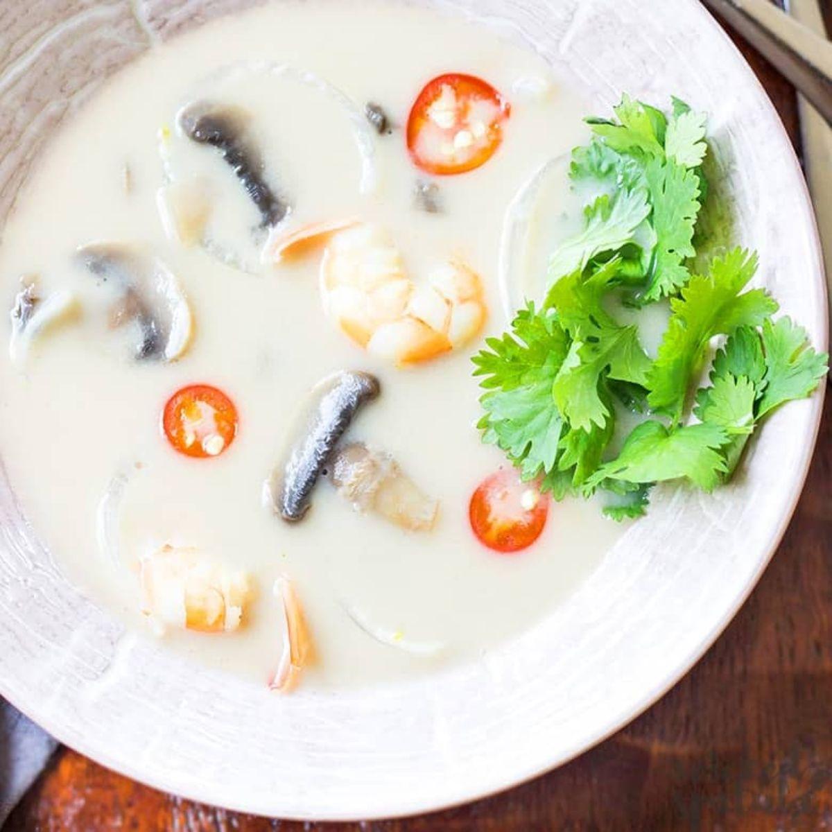 a white bowl of tom kha gai garnished with coriander