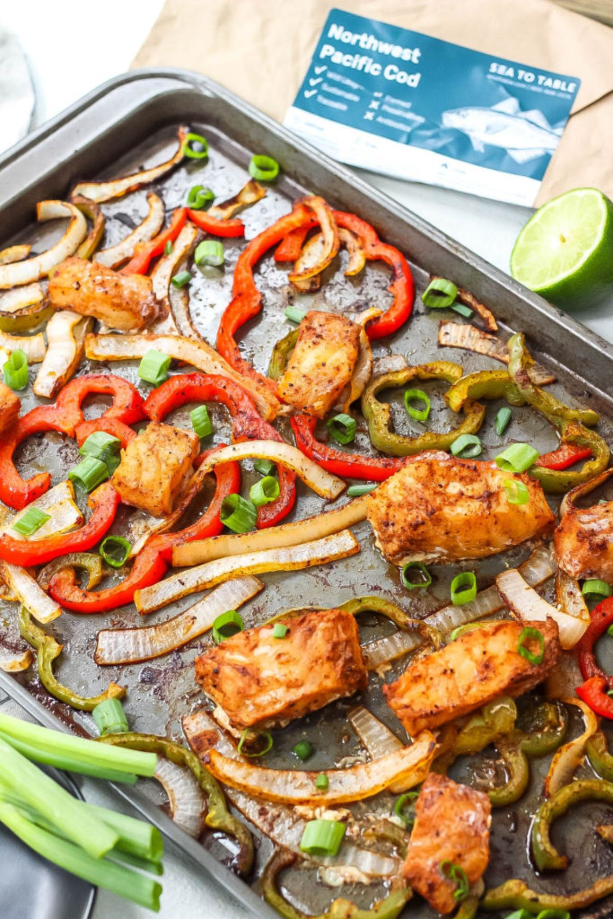 a sheet pan of fish, sliced peppers, scallions, and onions