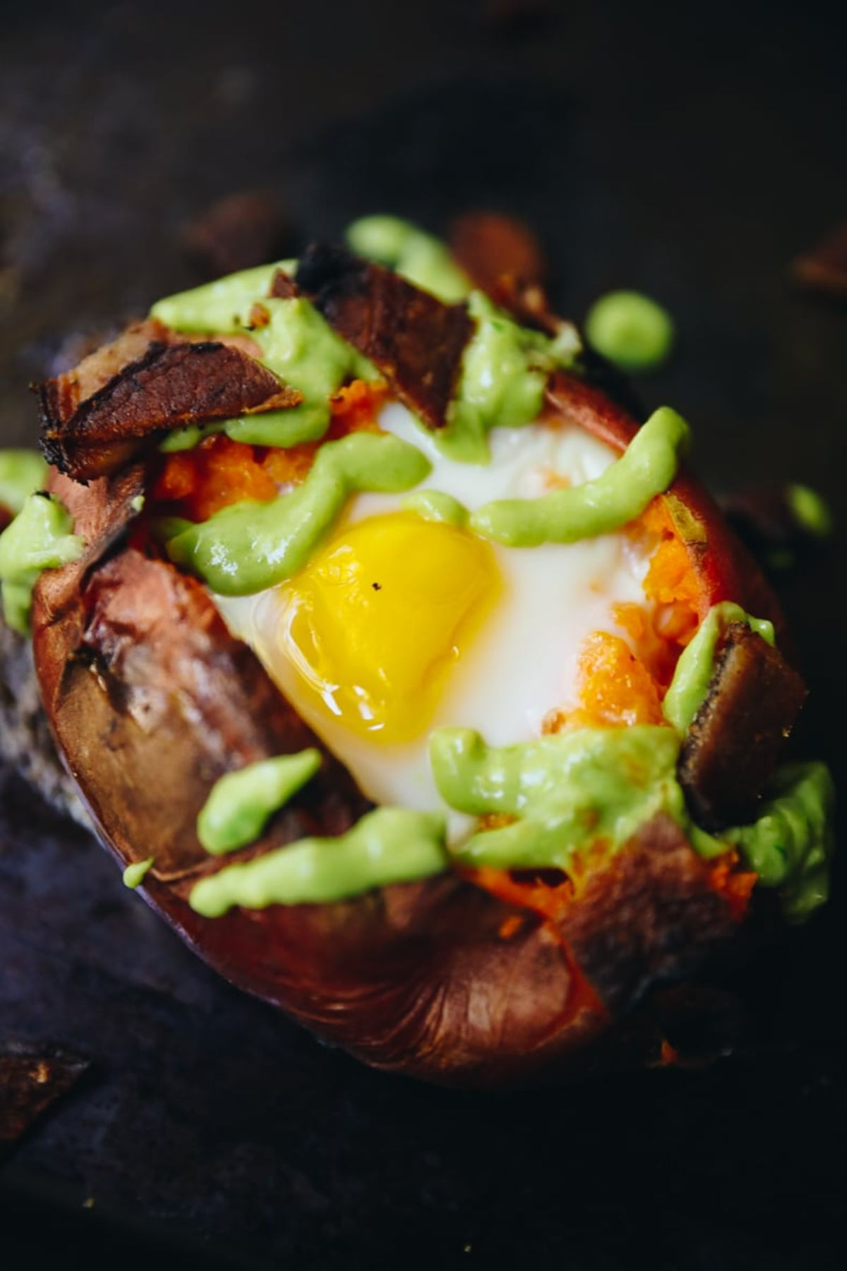 a sweet potato stuffed with a baked egg and drizzled with guacamole