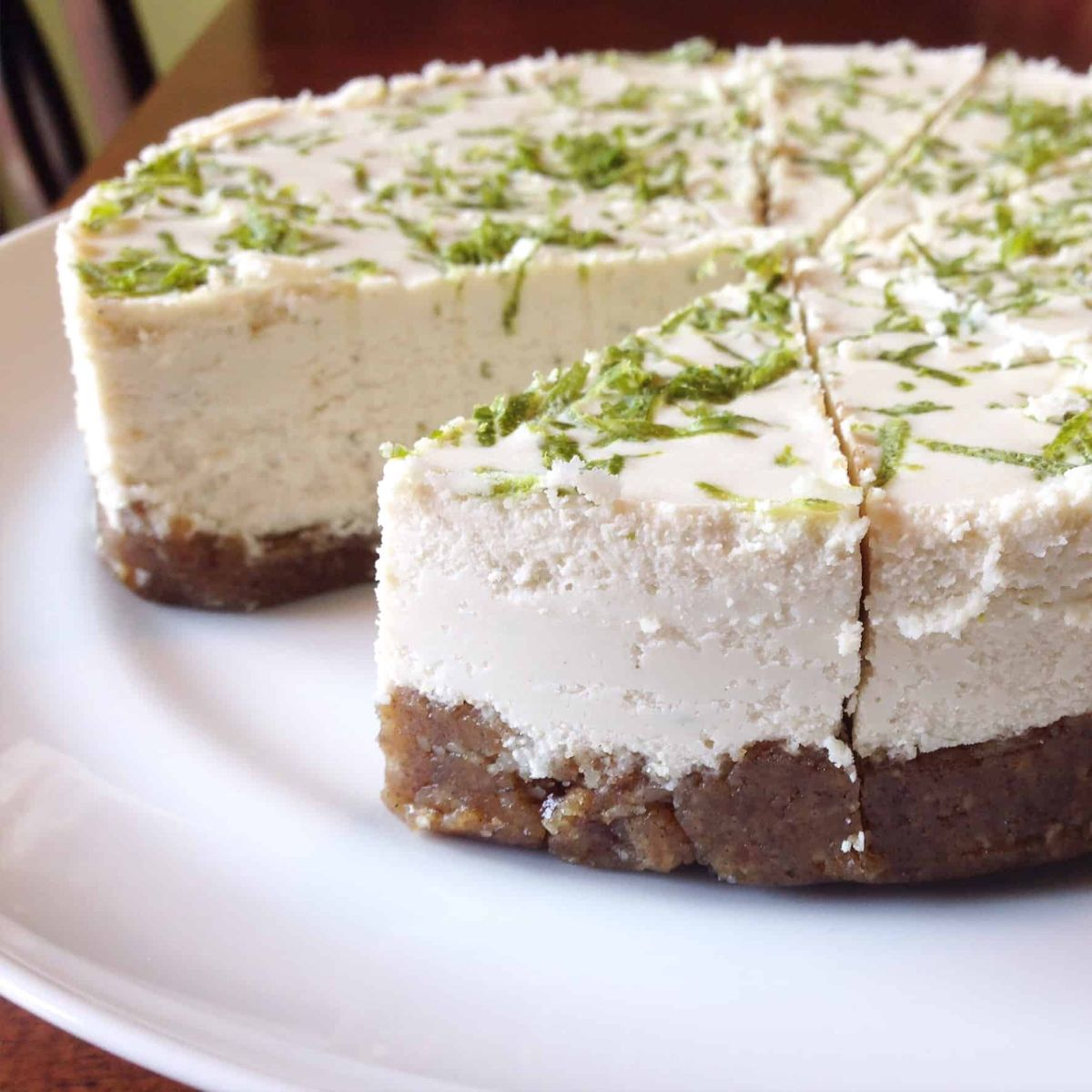 a key lime cheesecake cut into segments, with one missing. Lime zest is sprinkled on top