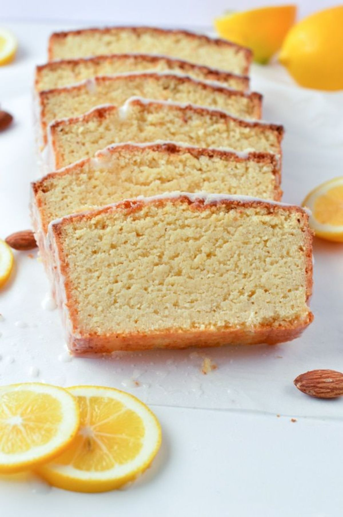 Slices of lemon cake with white icing. Lemon slices scattered around