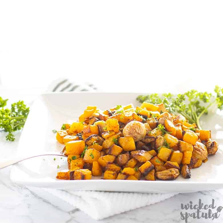garlic roasted butternut squash on a plate with a serving spoon