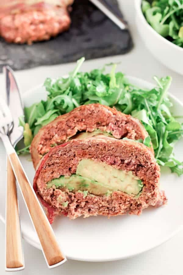Close Up Shot Of Mexican Style Chorizo Meatloaf Stuffed With Avocado and Served With Green Salad on White Plate