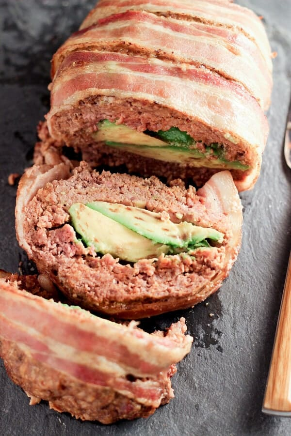 Overhead Shot Of Sliced Avocado Stuffed Mexican Meatloaf On Black Platter