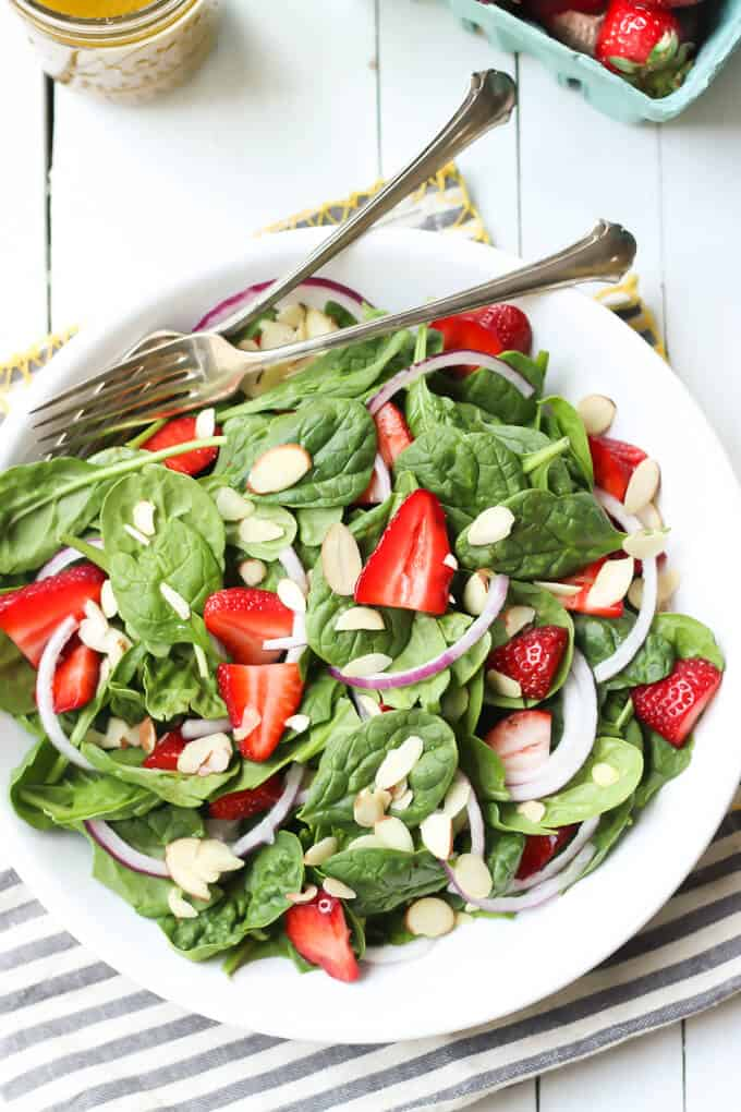 strawberry spinach salad with poppy seed dressing on a white plate with forks