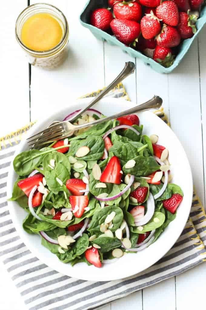 spinach strawberry poppyseed salad with pint of strawberries and dressing on the side