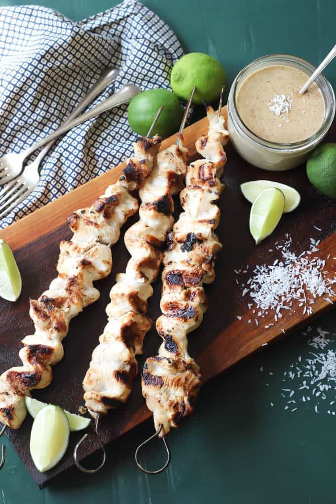 grilled Thai chicken satay skewers on a cutting board with limes