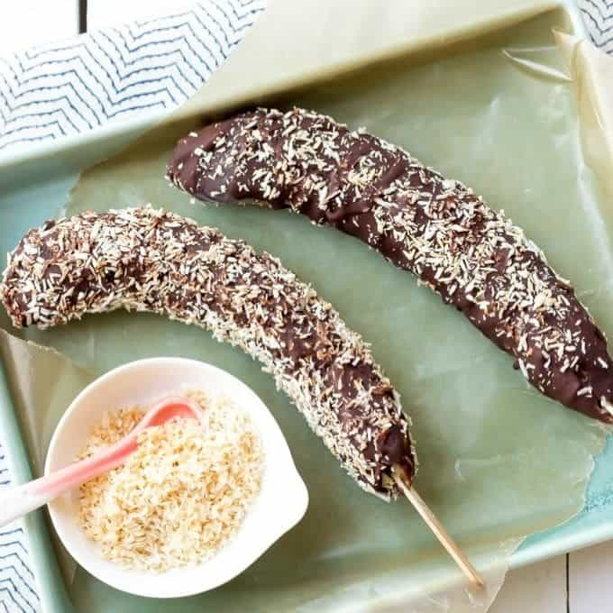 two frozen chocolate bananas with toasted coconut