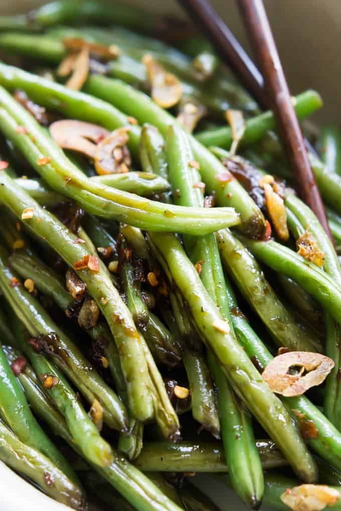 Close up image of spicy asian green beans in bowl with chopsticks