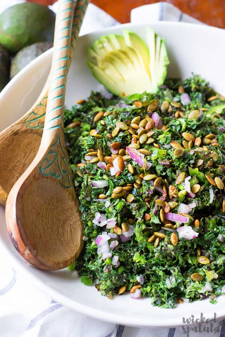 vegan kale Caesar salad in a bowl with wooden salad spoons